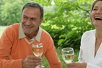 Laughing mature couple drinking white wine