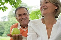 Toothy smiling mature man passing woman an apple