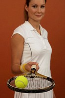 A female tennis player balancing a ball on a racket