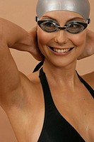 Smiling female swimmer wearing a bathing cap and goggles