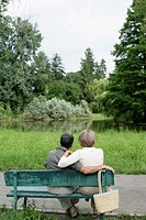 Mature couple sitting on a bench, looking at a small lake