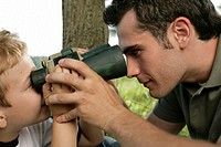 Son looking at father through binoculars