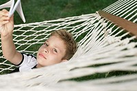 Boy lying in hammock, holding a paper plane in his hand