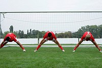 Three soccer players doing stretching exercise in front of the goal