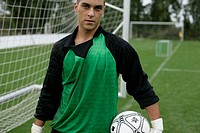 Goalkeeper with ball under his arm standing in front of a goal