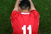 Soccer player wearing number 11 doing stretching exercise