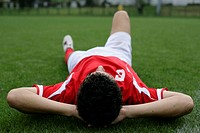 Soccer player lying on grass