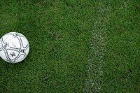 Football lying in the near of a strip on grass