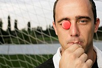 Referee with red chip in his eye whistling