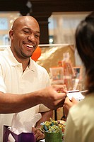 Young man handing a credit card to a sales clerk