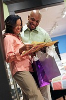 Young woman holding a book with a young man standing beside her in a store