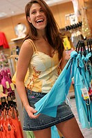 Young woman selecting clothes in a clothing store