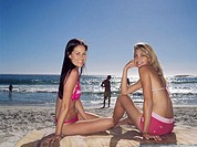 Side profile of two young women sitting on the beach (thumbnail)