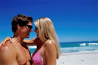 Side profile of a young couple embracing on the beach