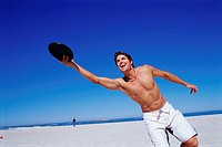 Young man playing frisbee on the beach