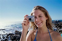Close-up of a young woman holding a digital camera