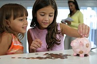 Two sisters looking at a piggy bank with their mother standing in the background