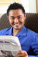 Portrait of a young man holding a newspaper smiling