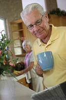Senior man holding a coffee cup reading a newspaper