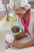 High angle view of a senior woman holding a piggy bank