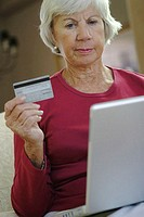 Senior woman sitting in front of a laptop holding a credit card