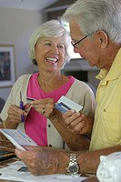 Close-up of a senior woman cutting a credit card with a pair of scissors
