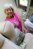 Low angle view of a senior woman hiding money under a cushion of an armchair
