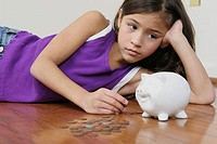 Close-up of a girl lying on the floor looking at a piggy bank