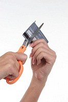 Close-up of a person's hand cutting a credit card with a pair of scissors