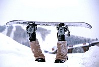 Person upside down in snow strapped to snowboard
