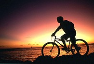 Person admiring sunset on mountain bike