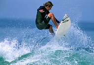 Side profile of a mid adult man surfing in the sea