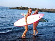 Portrait of two young women carrying surfboards on the beach