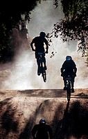 Silhouette of three people cycling in a race