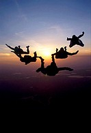 Silhouette of five people skydiving