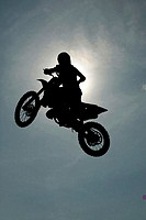 Silhouette of a person performing stunts on a motorcycle