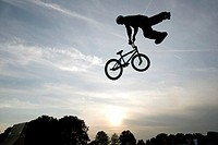 Silhouette of a person performing stunts on a bicycle