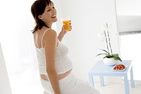 A pregnant woman drinking orange juice