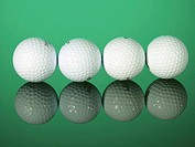 Four white golf balls on a shiny surface, close-up