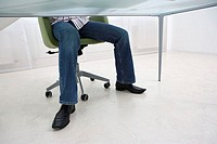 Legs of man under desk