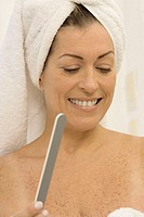 Mid adult woman smiling holding a nail file