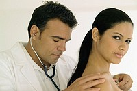 Male doctor listening to female chest with stethoscope