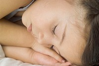 Young girl sleeping with head on hands, close up, side view