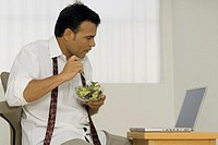 A man eating a bowl of salad and looking at a laptop