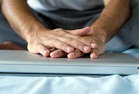 Hands folded across top of laptop computer, close-up