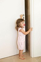 Young girl opening door