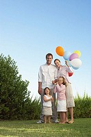 Portrait of family stood in garden with balloons