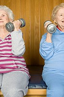 Two senior women lifting dumbbells