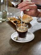 Man adding sugar to espresso coffee