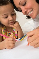 Woman and three year old girl coloring with markers, close-up, tilt